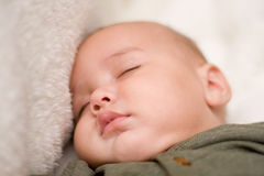 Sweet baby sleeping. A sweet baby face is sleeping. Infant is four months old and is multicultural, caucasian and asian. He has adorable pouty lips Royalty Free Stock Images