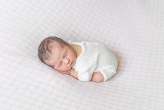 Sweet baby sleeping curled up on his belly Royalty Free Stock Photography