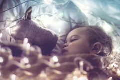 Sweet baby sleeping with soft toy. Sweet little baby boy sleeping with favourite soft toy, dreaming at home on magic night, vintage style fantasy photo stock photos