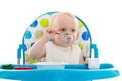 Sweet baby with spoon eats the yogurt. Sweet baby learning to eat with spoon sits on baby chair on a white background Royalty Free Stock Image