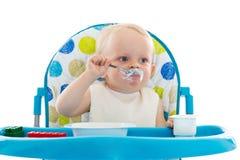 Sweet baby with spoon eats the yogurt. Royalty Free Stock Image