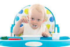 Sweet baby with spoon eats the yogurt. Sweet baby learning to eat with spoon sits on baby chair on a white background Royalty Free Stock Photo