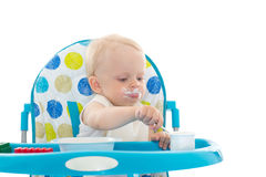 Sweet baby with spoon eats the yogurt. Stock Photo