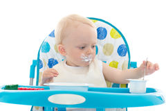 Sweet baby with spoon eats the yogurt. Royalty Free Stock Photo