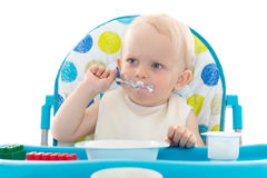 Sweet baby with spoon eats the yogurt. Sweet baby learning to eat with spoon sits on baby chair on a white background Stock Photography