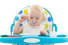 Sweet baby with spoon eats the yogurt. Sweet baby learning to eat with spoon sits on baby chair on a white background Stock Photo