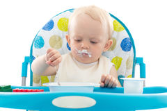 Sweet baby with spoon eats the yogurt. Royalty Free Stock Images