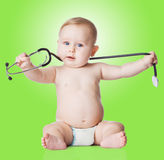 Sweet baby with stethoscope on a green background. Royalty Free Stock Photography