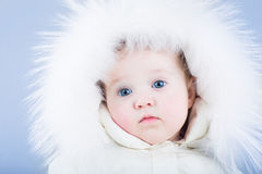 Sweet baby in a white snow suit with a fur hood looking tired Royalty Free Stock Photo
