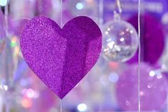 Purple heart paper mobile hanging from a string with bokeh lights stock images