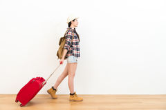 Sweet backpacker lady planning going to travel. Happy sweet backpacker lady planning going to travel and carrying personal suitcase walking on wooden floor with Royalty Free Stock Image