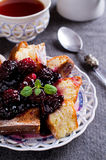 Sweet baked cake. With jam and berries on a dark background. Selective focus Stock Photos