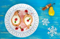 Sweet Baked pear with cream, raspberry syrup, fresh raspberries in sugar and mint leaves. Dessert on a blue wooden background. The top view Stock Photo