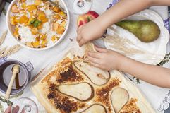 Sweet, baked pumpkin and pie with pear. Autumn dinner for the whole family. Children`s hands in the frame. Copy space.  stock image