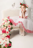 Sweet ballerina is sad. Sweet ballerina in a stage costume is sad beside the bouquets of spring flowers. Retro dress Stock Images