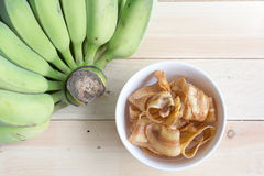 Sweet banana crisps on a bowl with wood background. Stock Image