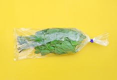 Sweet basil in plastic bag on yellow background (Pop art style) Royalty Free Stock Photography