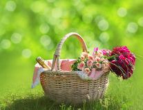 Sweet basket with bouquet of flowers on the grass Stock Images
