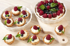 Sweet baskets with cream and raspberries and blueberry Stock Photos