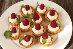 Sweet baskets with cream and raspberries and blueberry Royalty Free Stock Photography