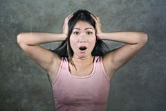 Sweet and beautiful Asian Korean girl gesturing shocked and surprised in astonished face expression on isolated grunge studio back. Young sweet and beautiful Royalty Free Stock Photography