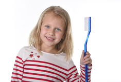 Sweet beautiful female child with blond hair and big blue eyes holding huge toothbrush smiling happy Stock Photos