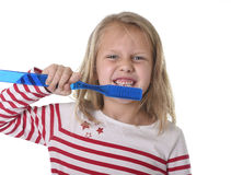 Sweet beautiful female child with blond hair and big blue eyes holding huge toothbrush smiling happy Royalty Free Stock Photography