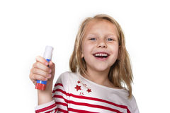 Sweet beautiful female child holding glue stick school supplies concept. Sweet beautiful female child 6 to 8 years old with cute blonde hair and blue eyes Stock Photo
