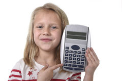 Sweet beautiful female child 6 to 8 years old holding calculator school supplies. Sweet beautiful female child 6 to 8 years old with cute blonde hair and blue royalty free stock photos