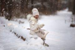 Sweet beautiful girl enjoying falling snowflakes in the park for walk. Sweet beautiful girl enjoying falling snowflakes in the park for a walk royalty free stock image
