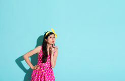 Sweet beautiful girl using mouth touching lollypop. Face to camera and wearing cute dress clothing standing in blue background Stock Photography