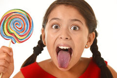 Sweet beautiful latin female child holding big lollipop candy eating and licking happy and excited Stock Photo