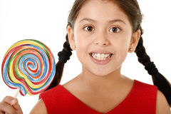 Sweet beautiful latin female child holding big lollipop candy eating and licking happy and excited Royalty Free Stock Images