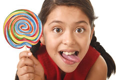 Sweet beautiful latin female child holding big lollipop candy eating and licking happy and excited Stock Photos