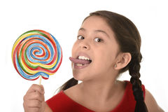 Sweet beautiful latin female child holding big lollipop candy eating and licking happy and excited Royalty Free Stock Image