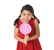 Sweet beautiful latin female child holding big pink spiral lollipop candy Royalty Free Stock Photography