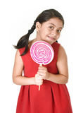 Sweet beautiful latin female child holding big pink spiral lollipop candy Royalty Free Stock Photos