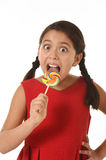 Sweet beautiful latin female child holding lollipop candy eating and licking happy and excited Stock Image