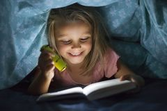 Sweet beautiful and pretty little blond girl 6 to 8 years old under bed covers reading book in the dark at night with torch light stock images