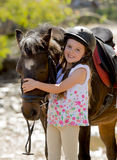 Sweet beautiful young girl 7 or 8 years old hugging head of little pony horse smiling happy wearing safety jockey helmet in summer Royalty Free Stock Photo
