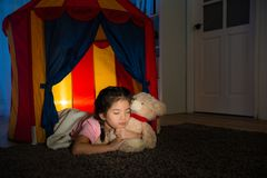 Sweet beauty kid lying sleeping in children tent. And holding favorite teddy bear toy enjoying good nice dream at night on living room Stock Images