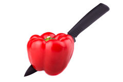 Sweet bell pepper pierced with a ceramic kitchen knife. On white background Royalty Free Stock Images
