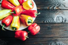 Capsicum yellow and red lie on white plate lie round. Sweet bell pepper on white plate on wooden background with clipping path - Red, Yellow, Orange Stock Images