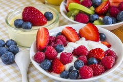 Sweet berries in small bowls with orange juice Stock Images