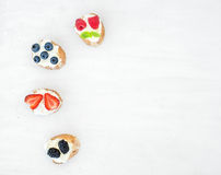 Sweet berry (strawberry, raspberry, blueberry and blackberry) an. D soft cheese sandwiches (bruschattas) over a white wooden background with a copy space. Top royalty free stock photo