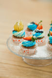 Sweet birthday cupcakes with berries and cream cheese. Sweet birthday cupcakes on a cake stand with berries and cream cheese. Decorated muffins on wooden table Stock Photos