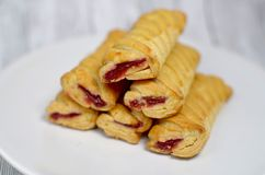 Sweet biscuits with jam on a white plate. On a table Stock Photo