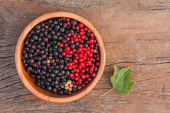Sweet, black and red currant and green leaves in wooden bowl. Stock Photo