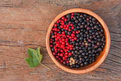 Sweet, black and red currant and green leaves in wooden bowl. Closeup. Selective focus Royalty Free Stock Image