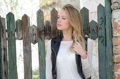 Sweet blond woman leaning against a fence Royalty Free Stock Images